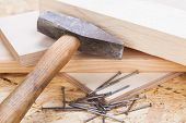 stock photo of joinery  - Mallet with nails and planks of new wood of varying thicknesses in a carpentry joinery DIY and building concept  - JPG