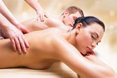 image of deep-tissue  - Beautiful couple lying  in a spa salon enjoying a deep tissue back massage together - JPG