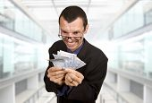 foto of greedy  - Greedy business man with money at the office - JPG