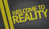 picture of realism  - Welcome to Reality written on the road - JPG