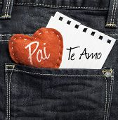 "picture of child missing  - ""Pai, Te Amo"" (In portuguese - Love You, Dad) written on a peace of paper and a heart on a jeans background - JPG"