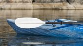 foto of kayak  - Selective focus on the paddle and kayak with water drops hitting the calm lake