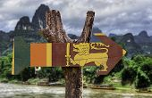 stock photo of sinhala  - Sri Lanka wooden sign with rural background - JPG