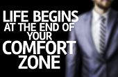 stock photo of comfort  - Life Begins at the end of Your Comfort Zone written on a board with a business man on background - JPG
