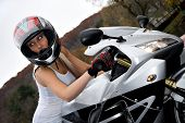 stock photo of crotch-rocket  - A pretty blonde girl seated on a modern motorcycle - JPG