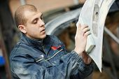 pic of buff  - auto mechanic worker sanding polishing bumper car at automobile repair and renew service station shop by sandpaper - JPG