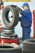 picture of lubricant  - Auto repairman lubricating automobile car wheel during tyre fitting or tire replacing - JPG