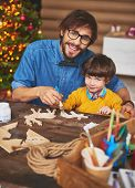 pic of deer family  - Handsome man and his son looking at camera while painting wooden deers - JPG