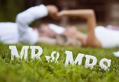 pic of lie  - Happy bride and groom enjoying their wedding day in green nature, lying on grass