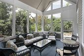 foto of screen-porch  - Porch in suburban home with wicker furniture - JPG
