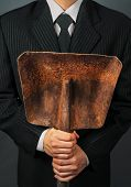 picture of power-shovel  - Businessman in a suit holding metal shovel face is not visible - JPG