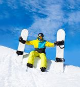 image of snowboarding  - snowboarder hold two snowboards sitting on snow mountain slope copy space blue sky - JPG