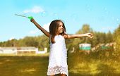 stock photo of have sweet dreams  - Little child having fun outdoors with soap bubbles - JPG