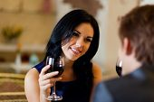 stock photo of romantic  - Young happy couple romantic date drink glass of red wine at restaurant - JPG
