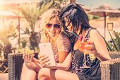 stock photo of two women taking cell phone  - Two girls looking at phone outdoor drinking cocktails - JPG