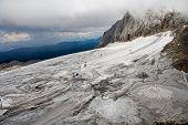 image of thunderhead  - grey thunderhead racks over the snowy mountain - JPG