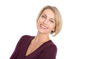 stock photo of maturity  - Lucky isolated blond mature woman with white teeth and pullover in bordeaux color - JPG