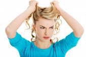 pic of pulling hair  - Portrait of angry woman pulling her hair - JPG