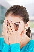 foto of peeking  - Shy teenage girl peeking through covered face - JPG