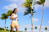 picture of florida-orange  - Asian runner girl jogging in tropical nature park outdoors with palm trees background during summer - JPG