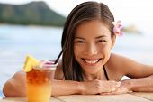 stock photo of beachfront  - Hawaii Asian tourist woman with hawaiian Mai Tai drink on beach swimming in infinity pool in bikini at beachfront resort with alcoholic cocktail made with pineapple juice - JPG