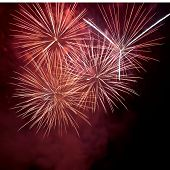 stock photo of firework display  - Red colorful fireworks on the black sky background - JPG