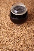 pic of malt  - Snifter glass with black stout beer standing over malted barley grains - JPG