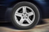 foto of alloy  - Modern automotive wheel on light alloy disc with blurred car background - JPG