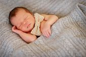pic of sleeping baby  - on a bed in a knitted blanket sleeping baby - JPG