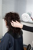 stock photo of hair blowing  - Stylist blow drying hair of a client at the beauty salon - JPG