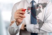 foto of aeroplane symbol  - Young business man drawing an airplane routes on world map - JPG