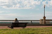 image of lonely woman  - lonely woman sitting on public bench near terrace with sea view loneliness