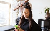 beauty, hairstyle and people concept - happy young woman with smartphone and hairdresser making hair poster