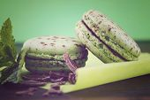 pic of mint-green  - Chocolate and mint flavor macaroons on dark wood table and green background with applied retro vintage style filters - JPG