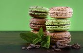 stock photo of mint-green  - Chocolate and mint flavor macaroons on dark wood table and green background - JPG