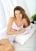 image of nightgown  - young attractive and beautiful woman in nightgown lying on bed at bedroom writing diary with pen in relax looking tranquil and happy in American lifestyle concept - JPG