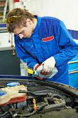 picture of auto repair shop  - auto repairman mechanic worker changing antifreeze in car auto repair or maintenance shop service station - JPG