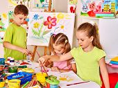 foto of nursery school child  - Child painting at easel in school - JPG