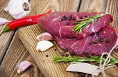 stock photo of beef shank  - Fresh beef steak with spices on a wooden background - JPG