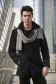 pic of coat  - Stylish Young Handsome Man in Black Coat Standing in City Center Street with Skyscraper Behind Him Looking to the Camera - JPG