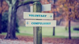 stock photo of opposites  - Signpost in a park or forested area with arrows pointing two opposite directions towards Voluntary and Compulsory retro effect faded look - JPG