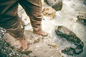 picture of survival  - Feet Man trekking boots hiking outdoor Lifestyle Travel survival concept with river and stones on background top view - JPG