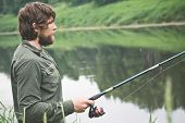 stock photo of survival  - Young Man Fisherman bearded fishing with rod Lifestyle Travel survival concept river on background - JPG