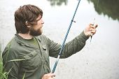image of survival  - Young Man Fisherman bearded fishing with rod Lifestyle Travel survival concept river on background - JPG