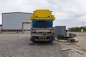 stock photo of boom-truck  - An industrial crane from behind with a container and a building - JPG