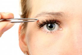 picture of eyebrows  - Young woman plucking eyebrows with tweezers close up - JPG