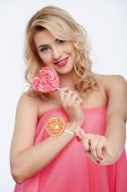 picture of lollipops  - Beautiful girl is touching lollipop in shape of heart to her cheek - JPG