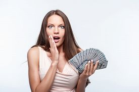 picture of shock awe  - Pretty girl is holding dollars in her left hand - JPG