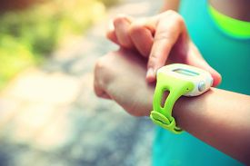 stock photo of jogger  - young woman jogger ready to run set and looking at sports smart watch checking performance or heart rate pulse trace. Sport and fitness outdoors on forest trail. ** Note: Shallow depth of field - JPG