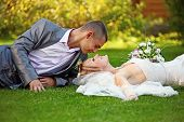 stock photo of married couple  - Portrait of happy newlyweds on grass in park - JPG